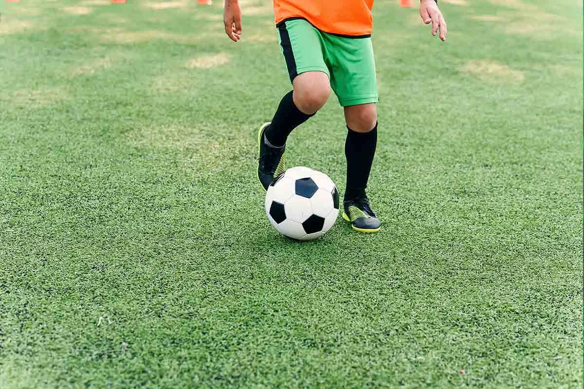 grama-sintetica-niño-futbol-balon